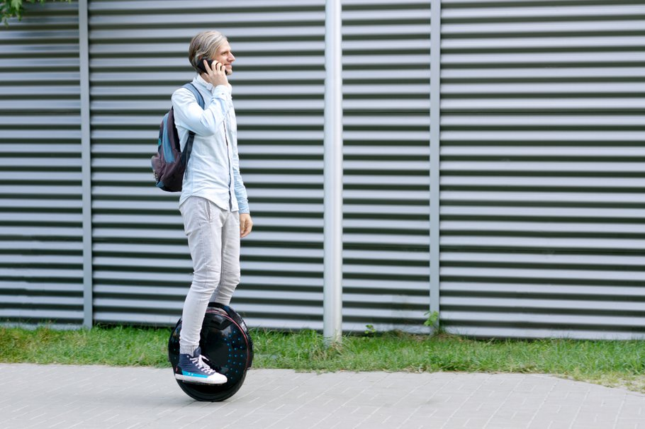 Modern young adult male businessman student freelancer riding driving on ecological electric transport futuristic eco electric unicycle scooter, balancing electric wheel with smartphone. Eco planet.