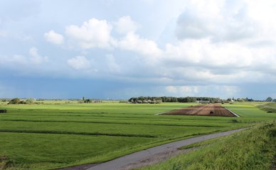 fields and meadows along dyke Hollandsche IJssel river with blue sky and whit clouds. The polder behind the dyke is named zuidplaspolder and the lowest area in the Netherlands with 21ft below sea