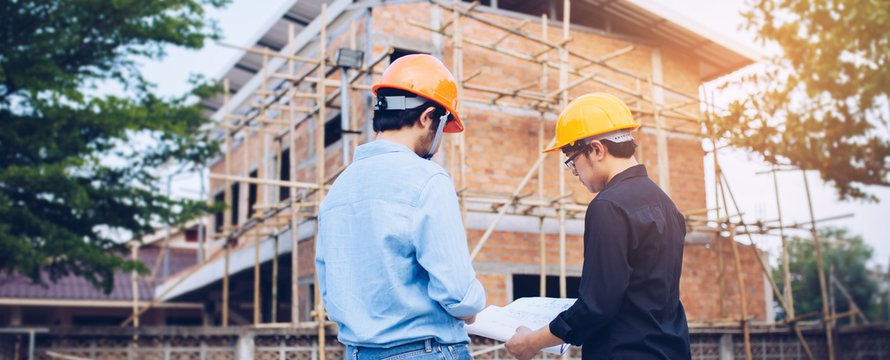 Two engineering man with helmet and paper work are discussing about the project over construction site background.