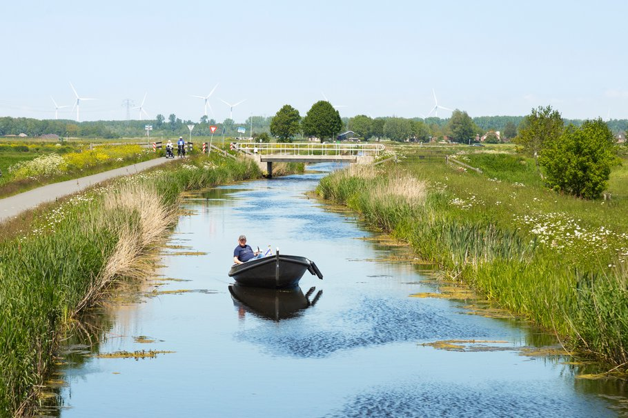 A small boat on the water and cyclists along the water in the nature reserve at Nijkerk.