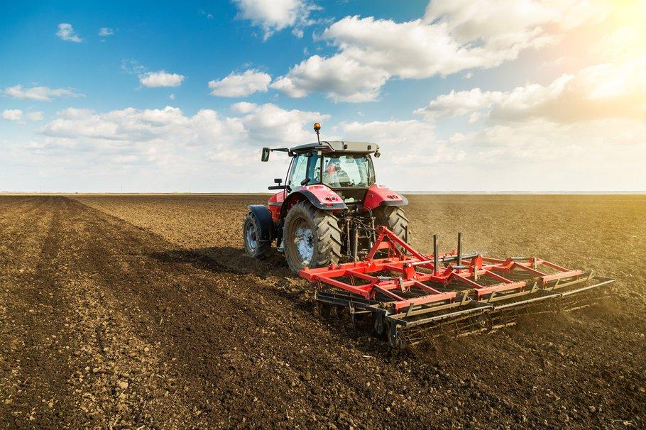 Landbouwer in tractor bereidt grond met zaaibedbebouwer als onderdeel van voorzaaiactiviteiten in het vroege voorjaar van landbouwwerken op landbouwgronden.