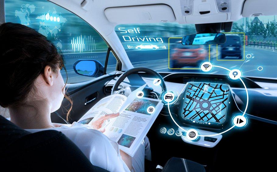 jonge vrouw het lezen van een boek in een autonome auto. bestuurderloze auto. zelfrijdend voertuig. heads up display. automotive technologie.