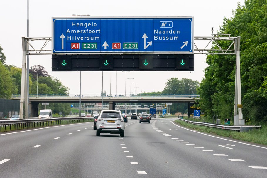 NAARDEN, NETHERLANDS - MAY 10, 2016: Traffic on motorway A1 and overhead route information signs, Naarden, North Holland